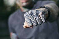 Close-up of clenched fist of tattooed young man outdoors - ZEDF01460