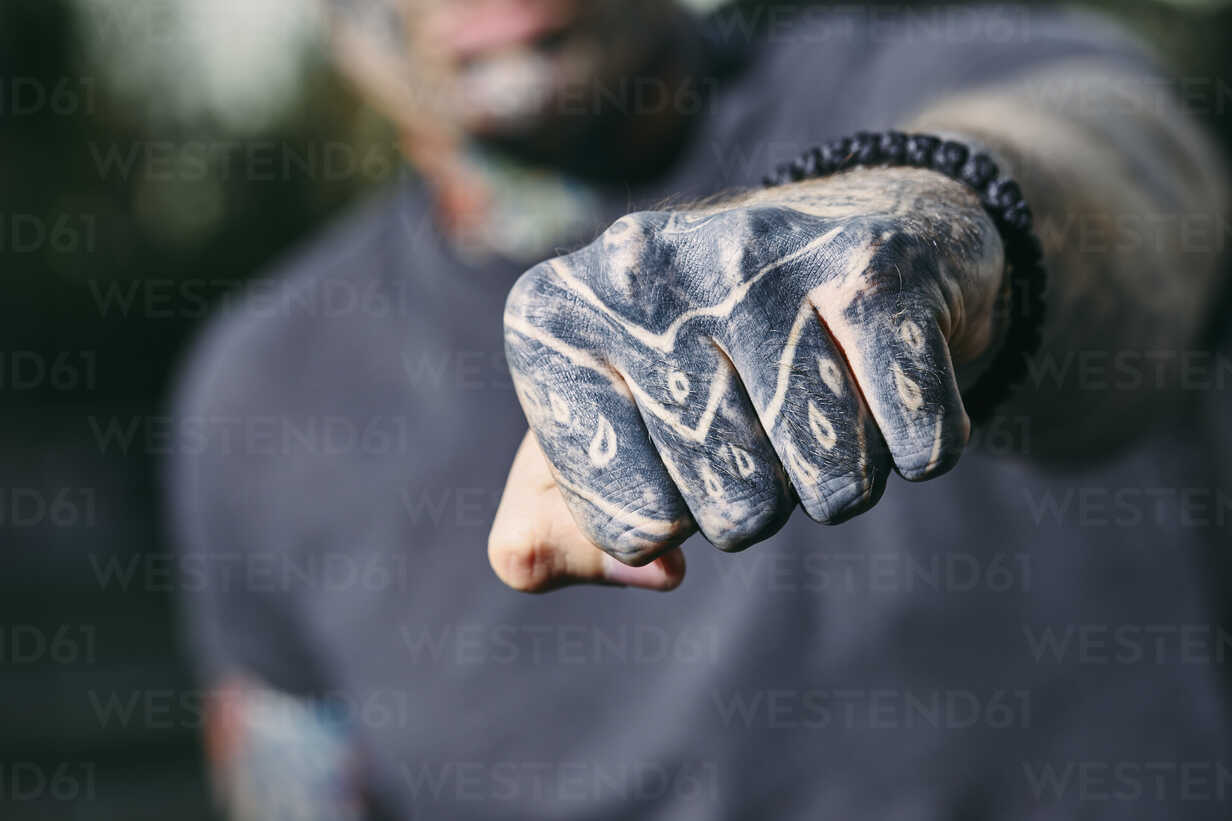 Close-up of clenched fist of tattooed young man outdoors - ZEDF01460 - Zeljko Dangubic/Westend61