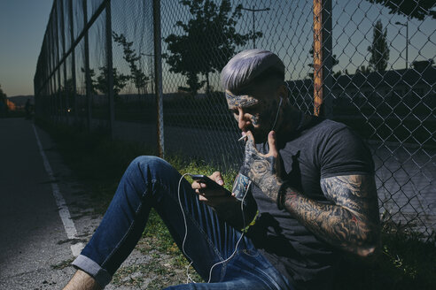Tattooed young man with earbuds and smartphone smoking a cigarette at wire mesh fence - ZEDF01469