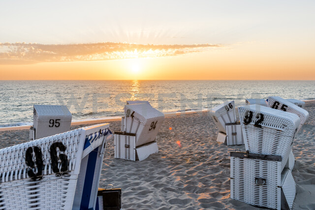 Germany, Schleswig-Holstein, Sylt, beach and empty hooded beach chairs at sunset - EGBF00251