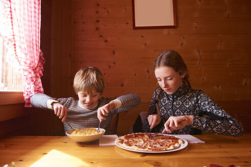 Teenage girl and brother eating pasta and pizza at chalet table - CUF04762