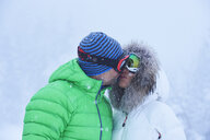 Mature couple kissing in falling snow, Gstaad, Switzerland - CUF04780
