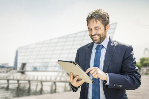 Businessman using digital tablet touchscreen on city waterfront - CUF04801