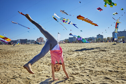 Young girl doing cartwheel on beach, kites flying in sky behind her, Rimini, italy - CUF04861