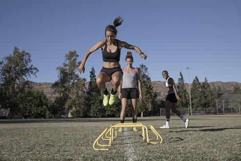 Woman jumping over agility hurdles - ISF01153