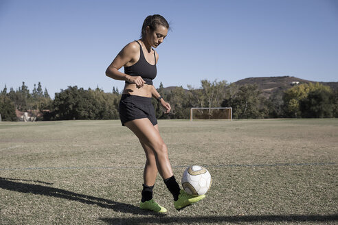 Woman on football pitch playing football - ISF01165