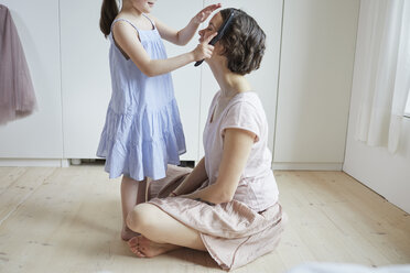 Mother sitting on floor, daughter brushing mother's hair, mid section - ISF01261