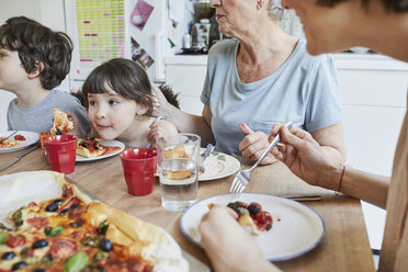 Three generation family sitting at kitchen table eating pizza - ISF01267