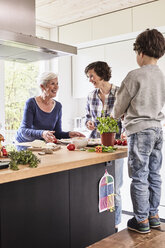 Young boy, mother and grandmother making pizza together in kitchen - ISF01273