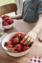 Young boy taking strawberry from bowl, mid section, close-up - ISF01279