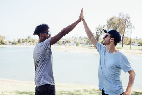 Friends doing high five by lake, Long Beach, California, US - ISF01297