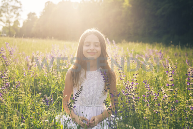 Portrait of smiling girl crouching on flower meadow at evening twilight - SARF03743