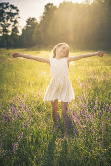 Happy girl dancing on flower meadow at evening twilight - SARF03746