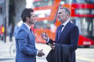 Businessmen in street talking, London, UK - CUF04894