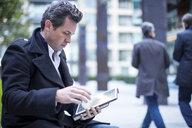 Businessman in street using digital tablet - CUF04897