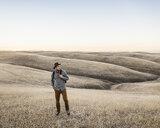 Man looking at rolling prairie hills, Bakersfield, California, USA - CUF04930