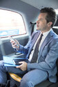 Mature businessman holding smartphone in taxi cab - CUF04945