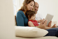 Baby girl sitting on sofa with parents looking at digital tablet - CUF05093
