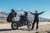 Woman standing next to touring motorbike. Lanin volcano in the back, Neuquen, Argentina - CUF05126