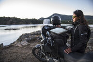 Woman standing next to touring motorbike at Lake Alumine, Neuquen Province, Argentina - CUF05129