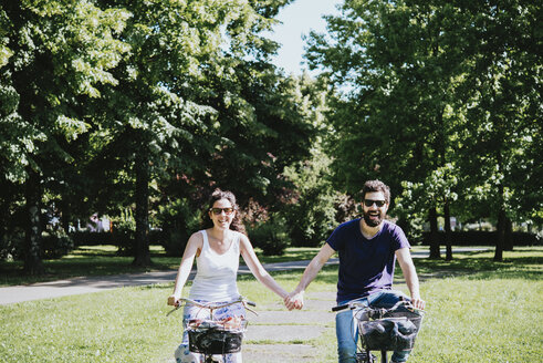 Couple holding hands while cycling in park, Arezzo, Tuscany, Italy - CUF05141