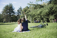 Rear view of couple taking smartphone selfie while sitting in park, Arezzo, Tuscany, Italy - CUF05147