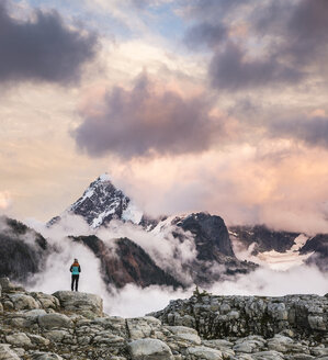 Hiker looking at clouds on snow covered mountains, Mount Baker, Washington, USA - CUF05186