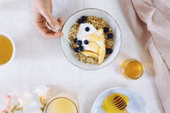 Overhead view of woman eating bowl of breakfast cereal topped with fruit - CUF05198