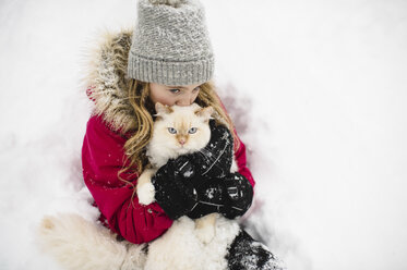 Portrait of green eyed white cat hugged by girl in snow - CUF05237