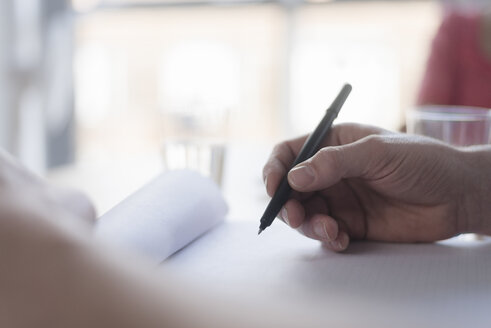 Man writing notes on desk, close up of hand - CUF05330