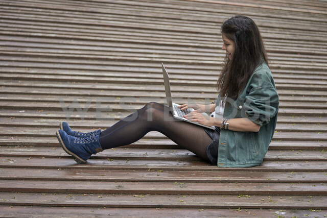 Young woman sitting on ground outdoors using laptop - BEF00044