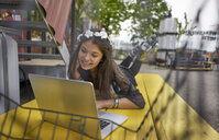 Smiling woman with inline skates lying on yellow table using laptop - BEF00047