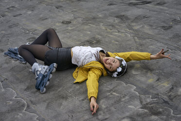 Screaming young woman with inline skates lying on ground listening music with headphones - BEF00050