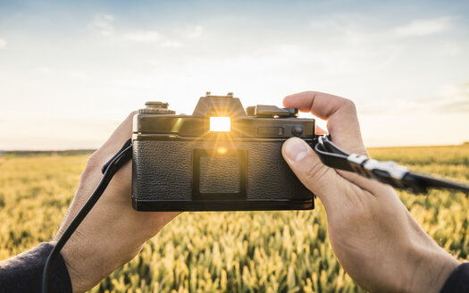 Man standing in field, holding SLR camera, sunlight shining through viewfinder, Neulingen, Baden-Württemberg, Germany - CUF05474