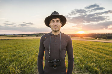 Portrait of mid adult man, standing in field, SLR camera around neck, Neulingen, Baden-Württemberg, Germany - CUF05477