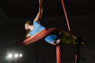 Young female aerial acrobat wrapped horizontally in silk rope - CUF05504