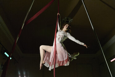 Low angle view of young female aerial acrobat hanging from silk rope - CUF05507