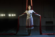 Portrait of young female aerial acrobat poised between red silk ropes - CUF05510