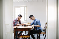 Male couple at home, young man sitting at table, reading book, partner look at smartphone - CUF05537