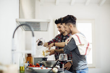 Male couple preparing meal together in kitchen - CUF05552
