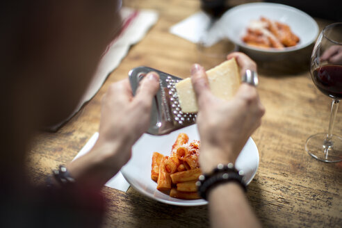 Man grating parmesan cheese on pasta, close-up - CUF05558