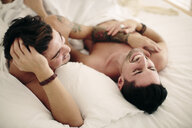 Male couple, partially dressed, relaxing in bed, laughing - CUF05576