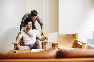 Young man at home, sitting in chair, using laptop, his partner hugging him from behind - CUF05582