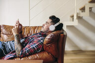 Man relaxing on sofa, wearing headphones, using smartphone - CUF05585