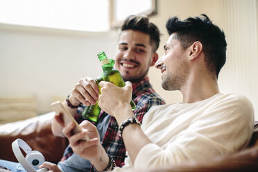 Male couple sitting on sofa, holding beer bottles, making toast, smiling - CUF05588