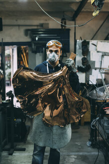 Portrait of metalworker holding copper product in forge workshop - CUF05645