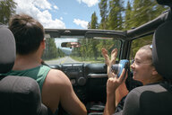Young woman with instant camera driving on road trip with boyfriend, Breckenridge, Colorado, USA - ISF01310