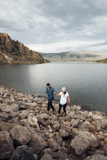 Couple walking on rocks beside Dillon Reservoir, elevated view, Silverthorne, Colorado, USA - ISF01358