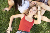 Portrait of young woman lying in grass with friends listening to music - IGGF00474