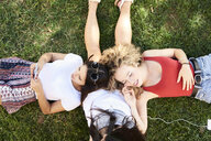 Three young women lying in grass using cell phone and listening to music - IGGF00477